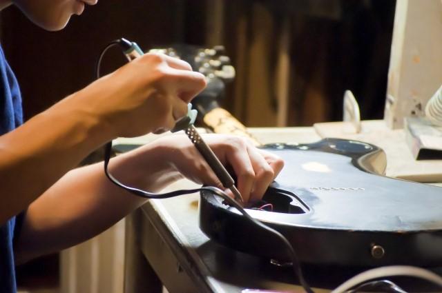 黒いエレキギターを修理中の男性