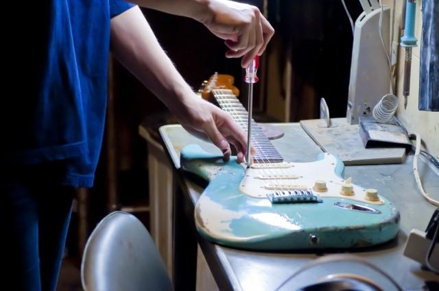 エレキギターをドライバーで修理している人