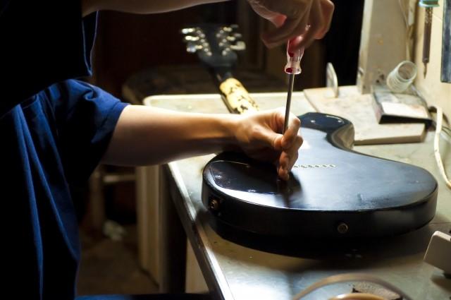 ギターの弦パーツを修理する男性