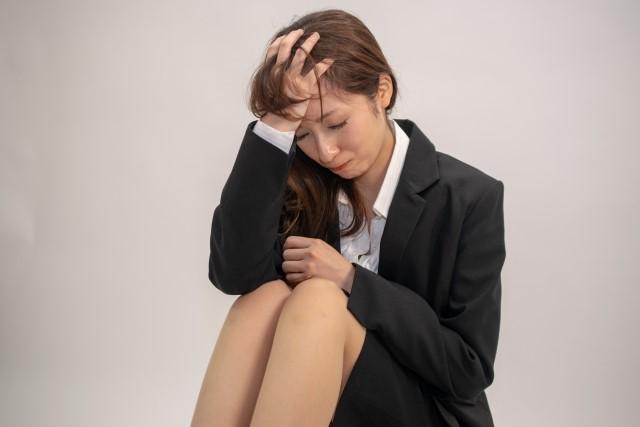 頭を抱えて悩む飲食店の社員を辞めたい女性