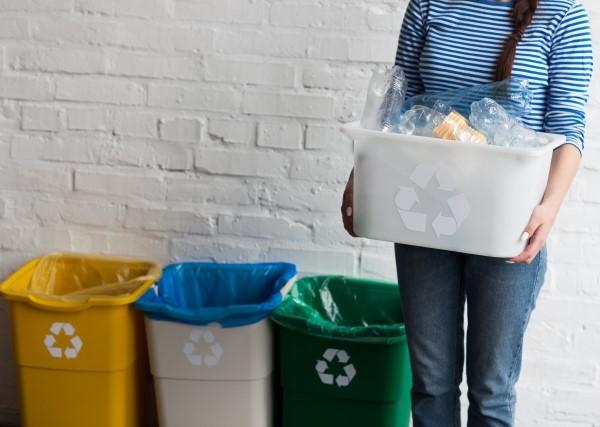 リユースマーク入りのゴミ箱と横に立つ巨乳女性