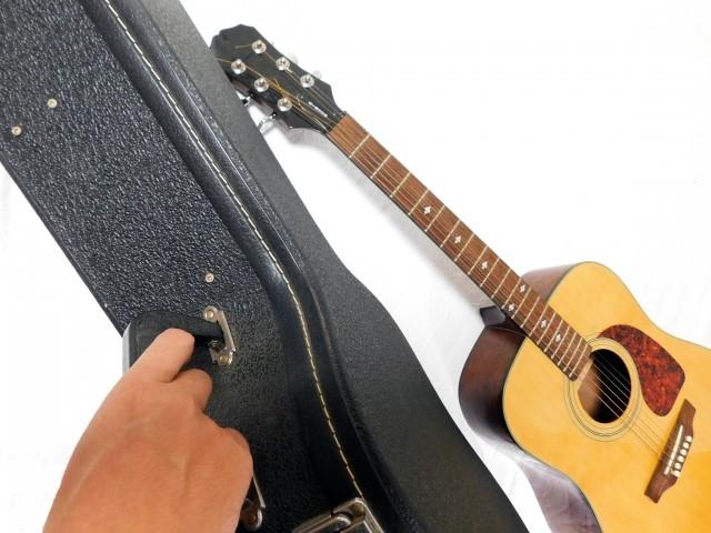 ギターとギターケースを持つ人