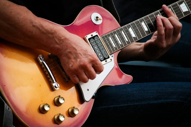 古いエレキギターを弾く人