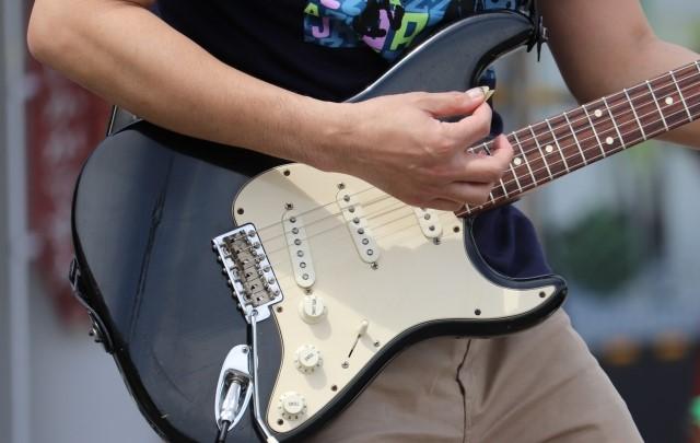 黒いエレキギターギターを弾く男性