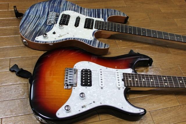 茶色いエレキギターと白いエレキギター