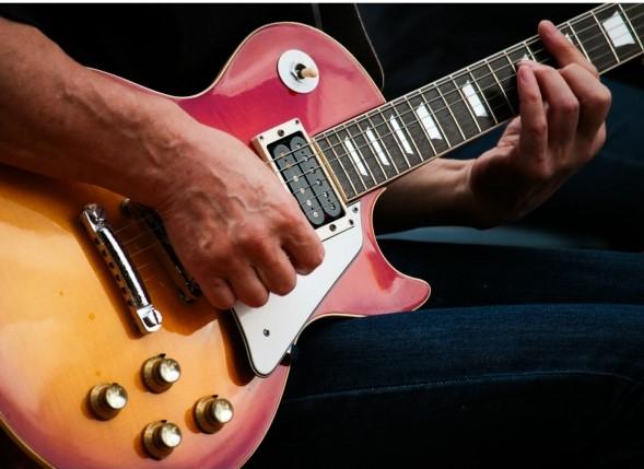 赤と黄色のギブソン・レスポールギターを弾く男性