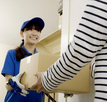 梱包されたギターを運ぶ宅配業者の女性