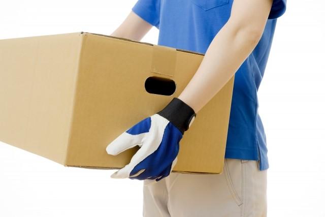 ギターを梱包して運ぶ宅配業者