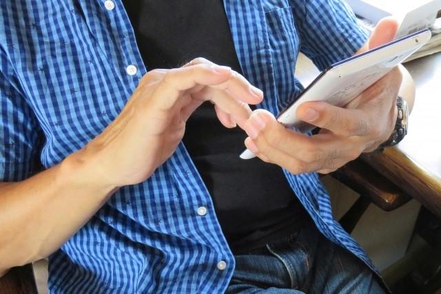 楽器買取専門店にスマホでメールを送る男性