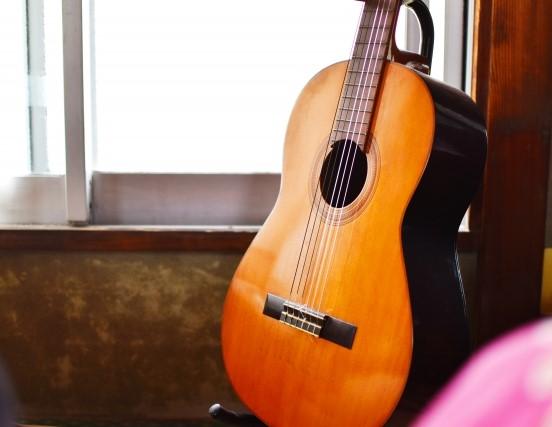 部屋の隅に置かれた古いアコースティックギター