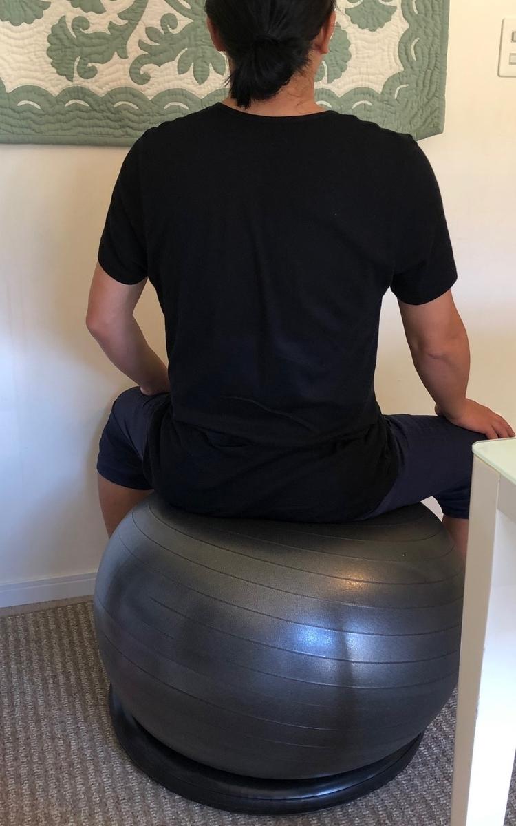 バランスボール「姿勢よしお」に座る男性