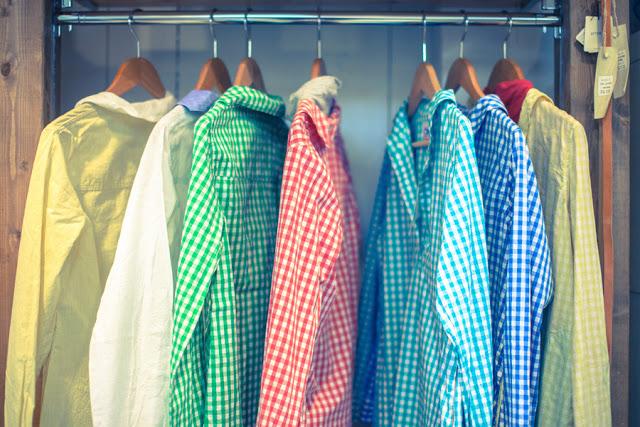 色とりどりのボタンダウンシャツが、ハンガーラックにかかっている