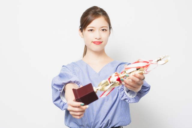 トロフィーを授与する女性の画像