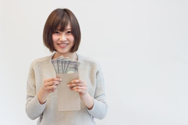 お金を手にする女性の画像