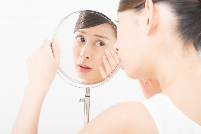 鏡に映る顔を気にする女性の画像