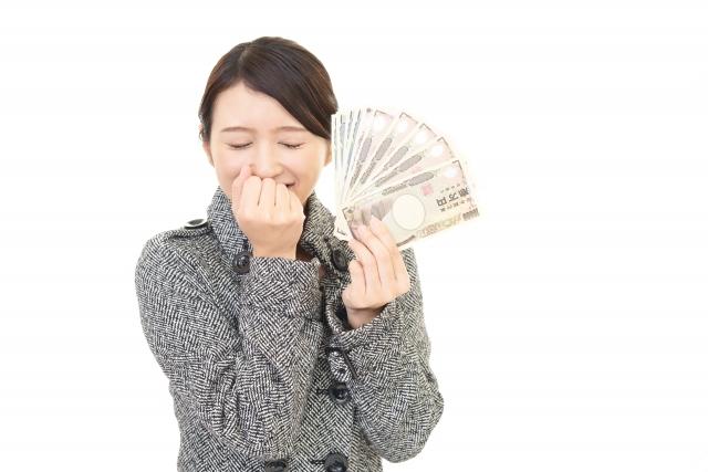 お金を握り締め笑う女性の画像