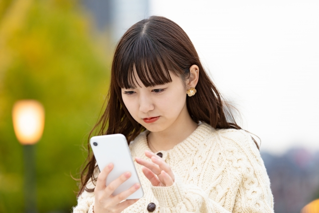 神妙な顔で携帯電話を触る女性