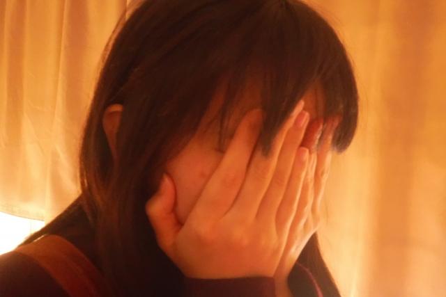 顔を覆う女性の画像