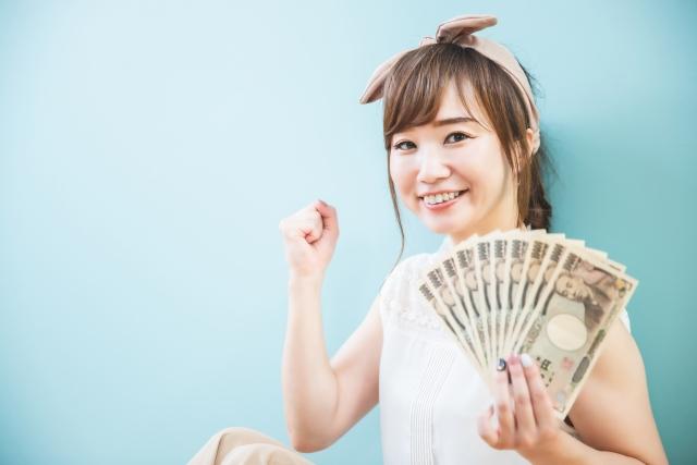 札束を手に持ってガッツポーズをする女性の画像