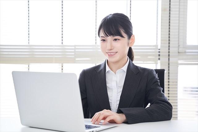 オフィスで笑顔でノートパソコンを操作する日本人女性ビジネスウーマンの画像