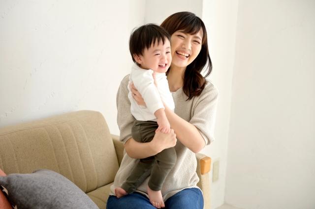 赤ん坊を抱っこし、笑顔の女性の画像