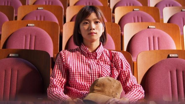 映画館で映画を見る女性の画像