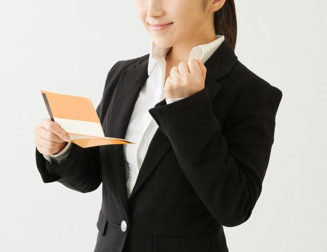 通帳を片手にガッツポーズの女性の画像