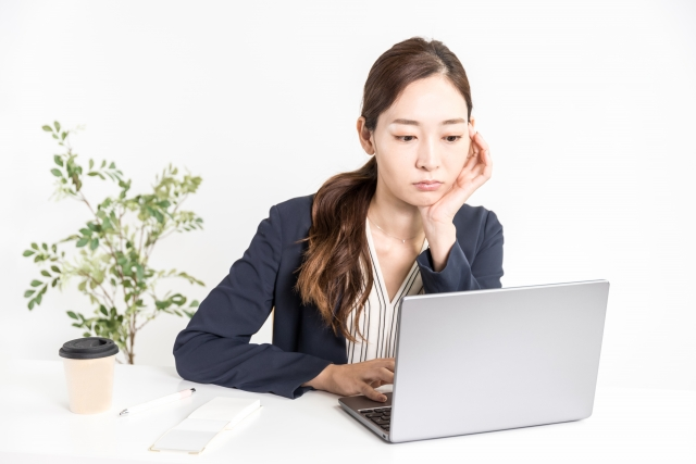 静かに怒りパソコンを操作する女性の画像
