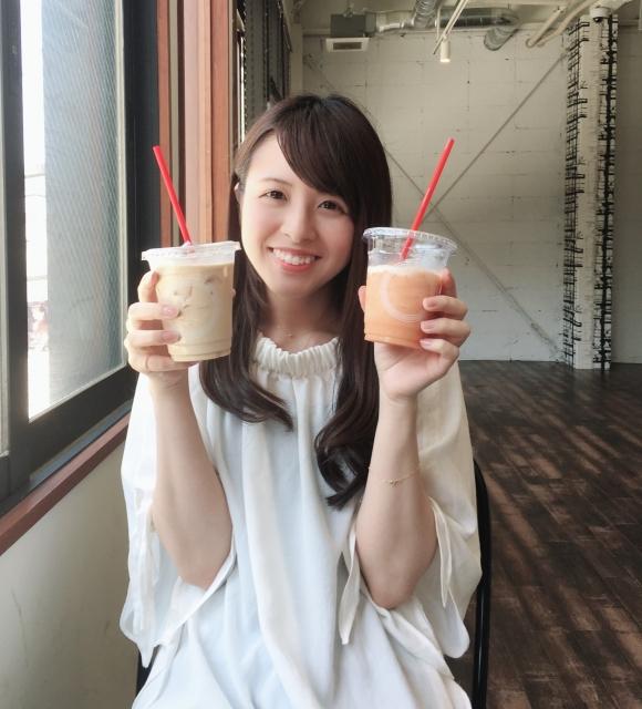 ジュースを両手に持ち笑顔の女性の画像