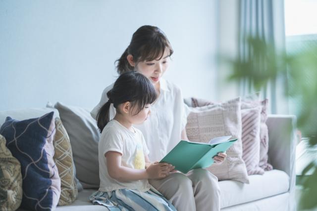 ソファに座って絵本を読む親子の画像