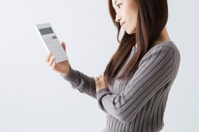 電卓を見て考える女性の画像