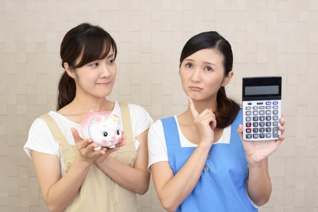 豚の貯金箱と計算機を持つ二人の女性の画像