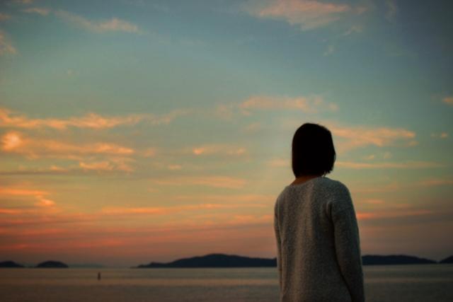 黄昏時と女性の背中の画像