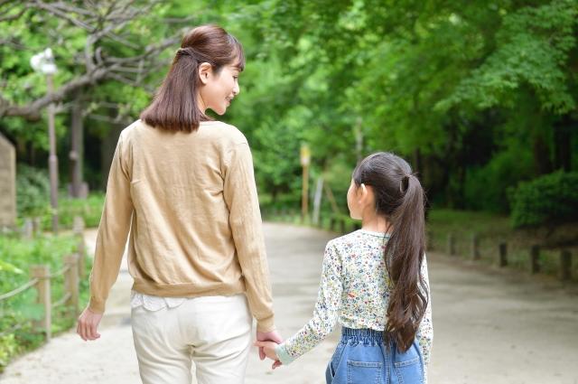 手を繋いで歩く母娘の画像