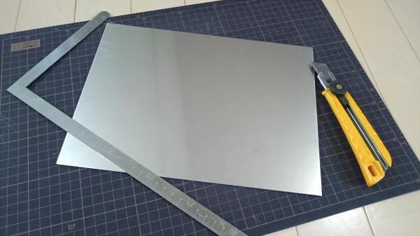 アルミ板とカッターマットとカッターナイフと金定規の写真