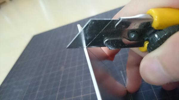 アルミ板の側面にカッターナイフの刃を当てている写真