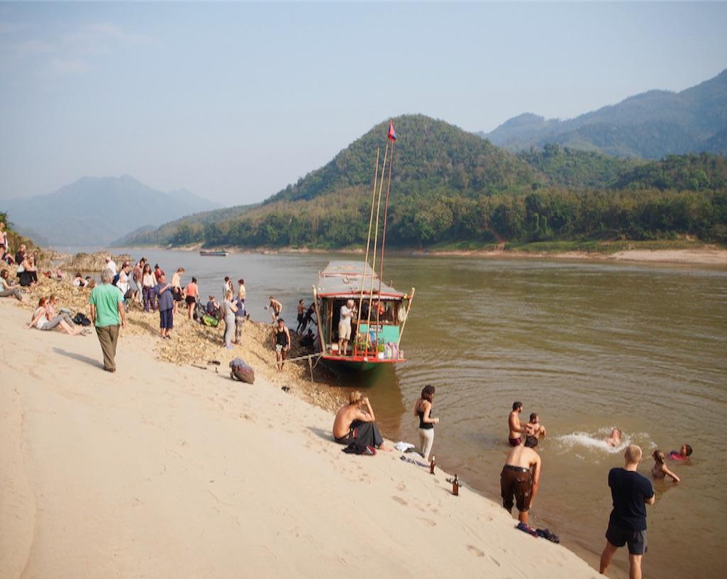 大浸水をチャンスに変えてメコン川を楽しむツーリストたち