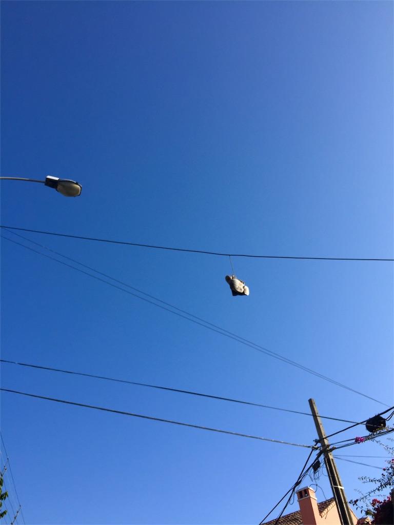 電線にスニーカーがぶら下がっている