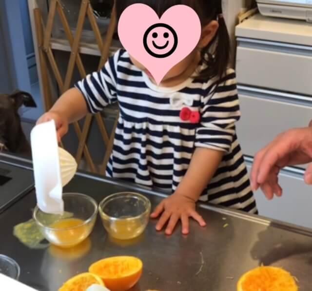 出来上がったオレンジジュースをコップに注ぐ