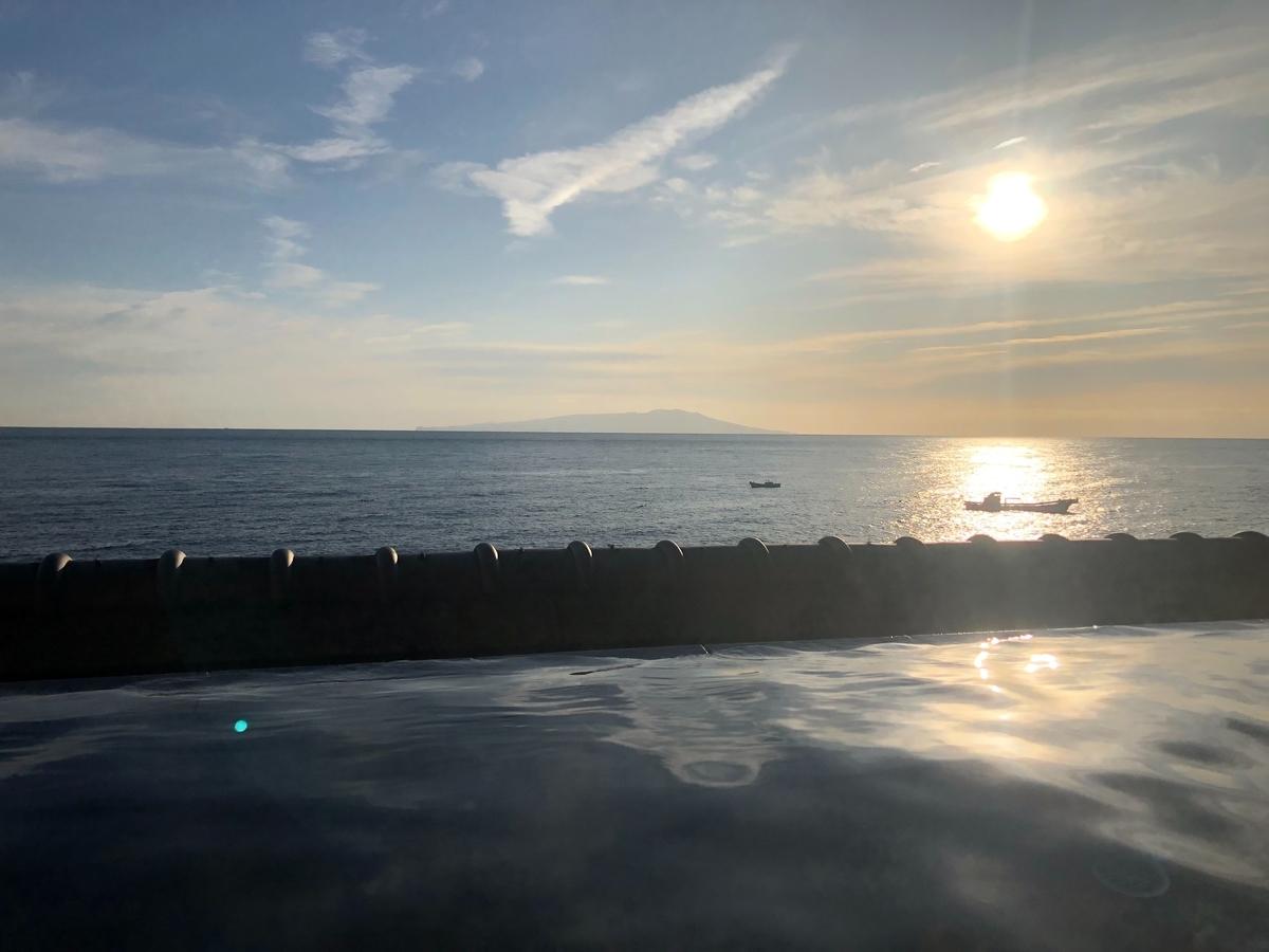 露天風呂の水面と朝日