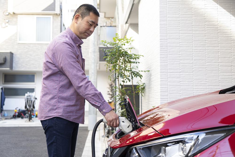 電気自動車に充電をする男性