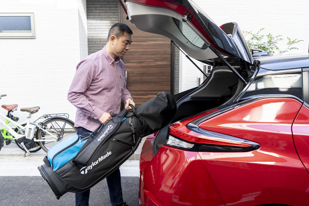 電気自動車のトランクにゴルフバッグをつむ男性