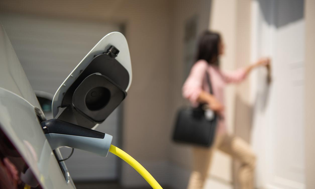 自宅で電気自動車を充電する女性