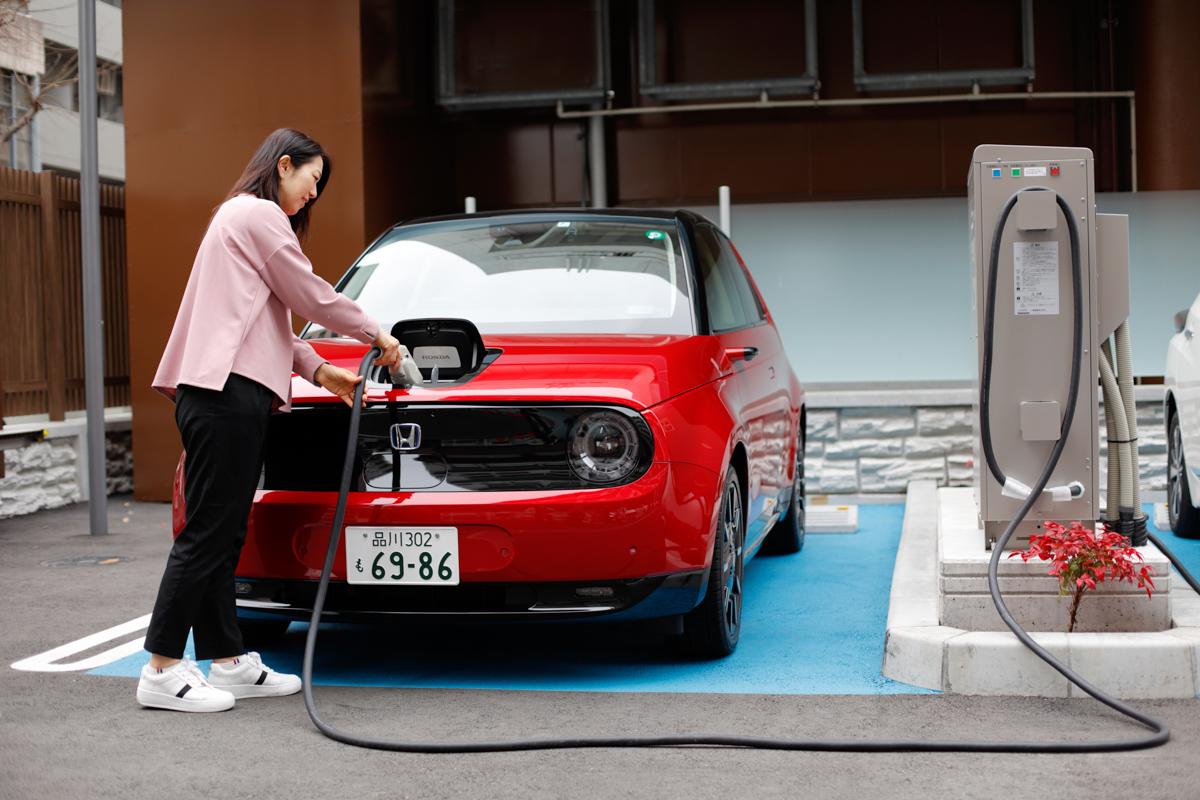 電気自動車(EV)に充電する女性