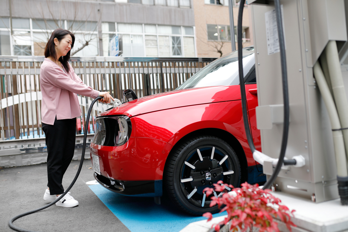 電気自動車(EV)を充電する女性
