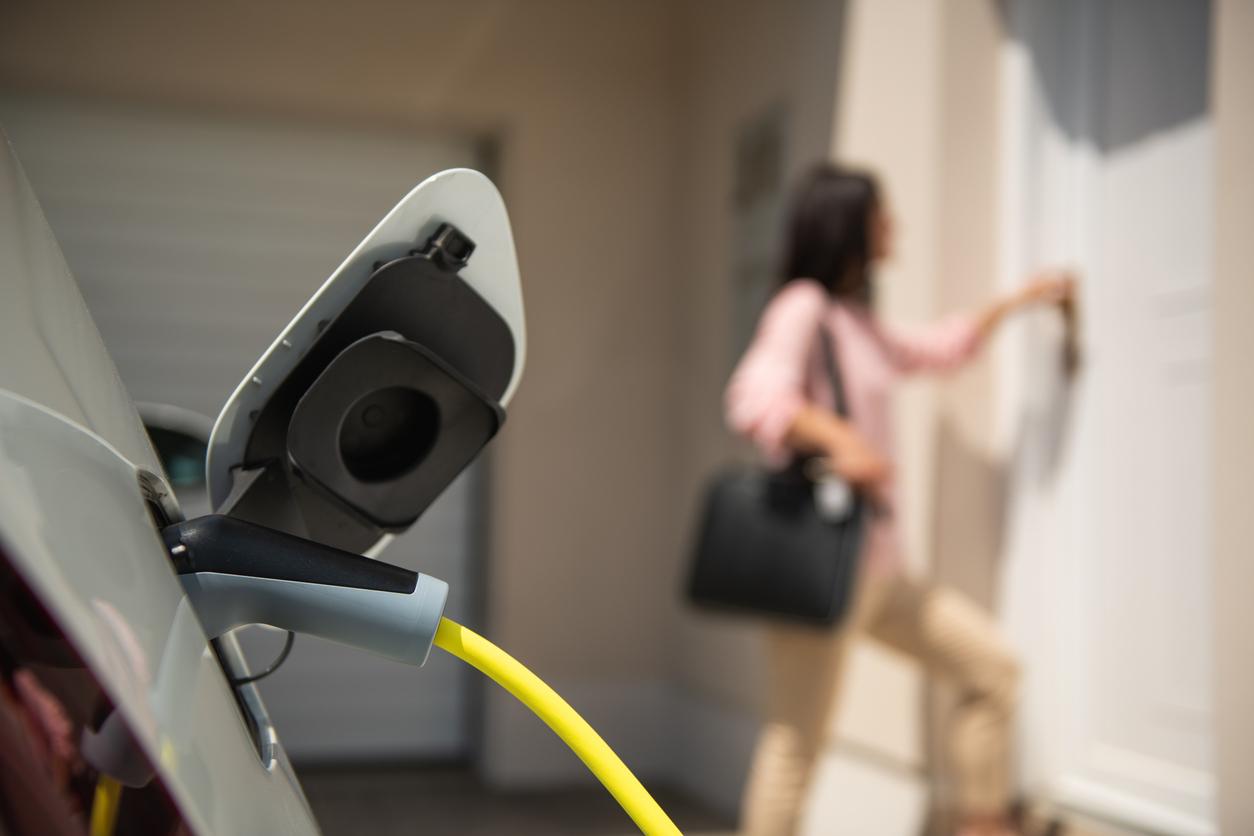 家で電気自動車と充電する女性