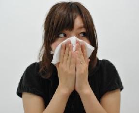 辛い鼻水にハンカチを顔に当てる女性