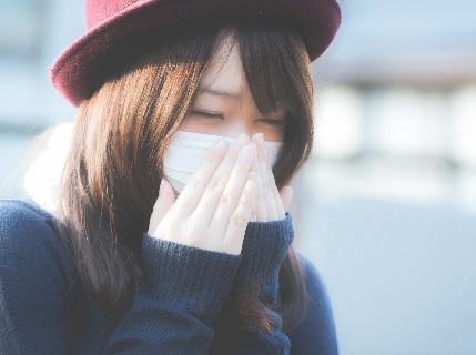 マスクをつけ繰り返すくしゃみに辛そうな女子
