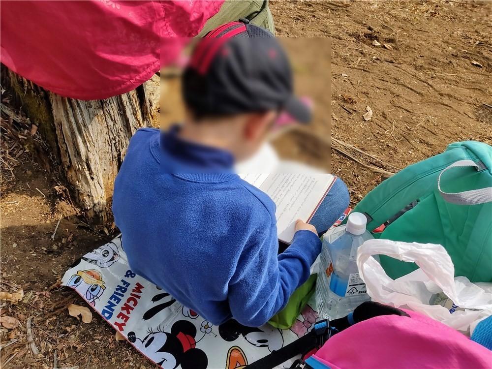 山頂で読書する息子