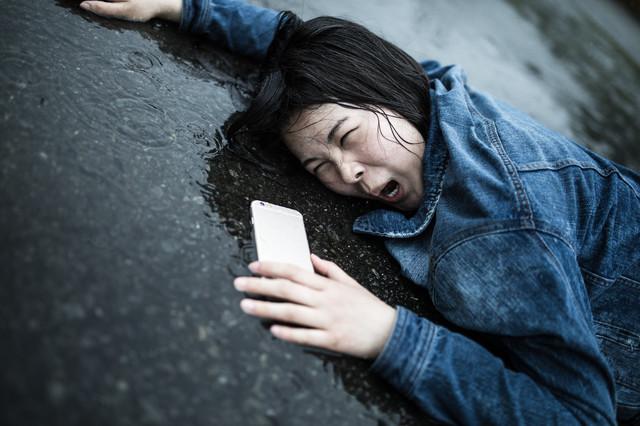 雨の中で倒れている女性
